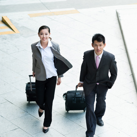workmates: young beautiful woman and businessman walking with luggages from top view