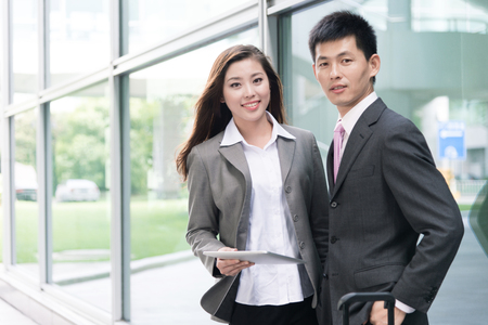 workmates: asian beautiful girl and businessman with tablet in modern hall
