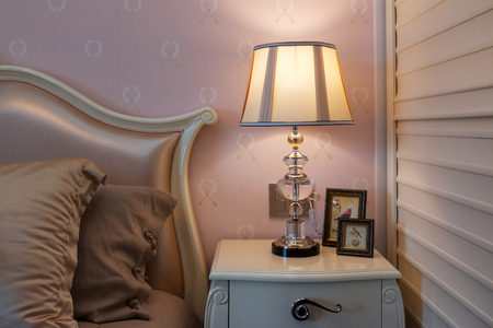 comfortable: elegant lamp on table near comfortable bed Editorial