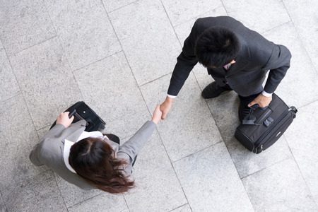 workmates: top view of woman is shaking hands with businessman Stock Photo