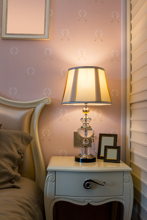 comfortable: elegant lamp on table near comfortable bed Stock Photo