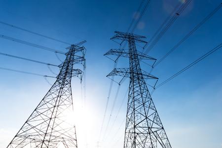 torres de alta tension: power pylons in field in sunny sky Foto de archivo