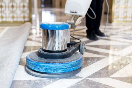 近代的なオフィスビルの大理石の床を磨く男