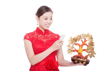 young asian woman in red cheongsam holds mobile phone and lucky tree in chinese new year