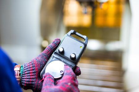 metro de medir: hand holds measuring meter in manufacturing factory Foto de archivo