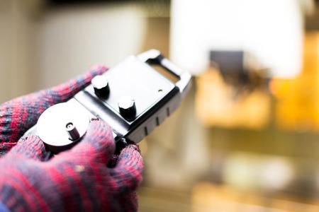 metro medir: hand holds measuring meter in manufacturing factory Foto de archivo