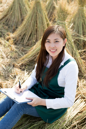 agronomist: young pretty chinese woman sits in golden cereal field
