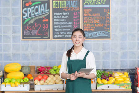 young pretty chinese woman works in fruit store