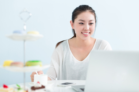 young pretty chinese woman working with laptop in office Stock Photo