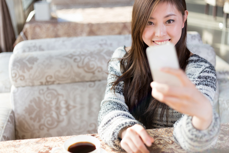 young pretty chinese woman sitting in modern cafe