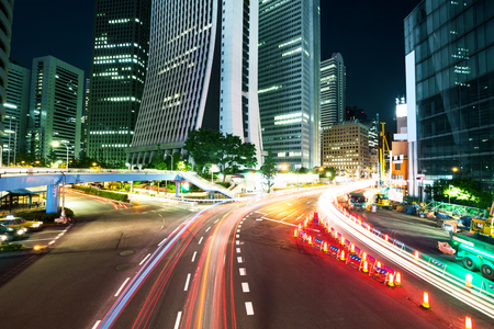 city traffic: modern office buildings in midtown of tokyo at night from busy road