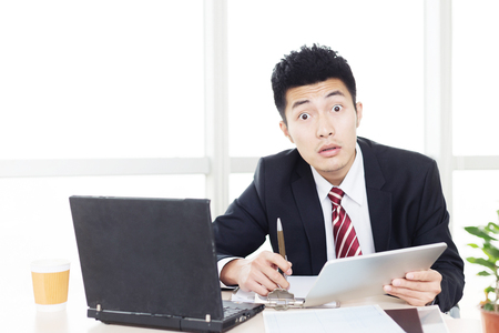 sittting: handsome chinese young businessman working with computer in modern office