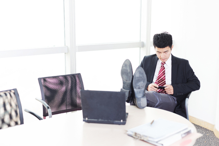 sittting: handsome chinese young businessman with digital tablet in modern office