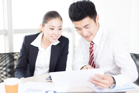 handsome chinese businessman and pretty chinese businesswoman with digital tablet in modern office Stock Photo
