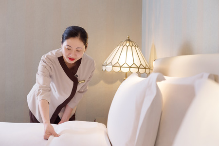 makes: young chinese woman housekeeper makes bed in modern hotel