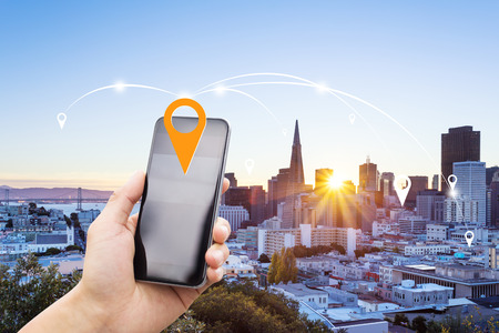 mobile phone with modern buildings in san francisco at sunrise