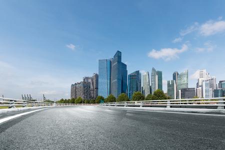 Estrada vazia com edifícios modernos em Cingapura Foto de archivo - 81054913