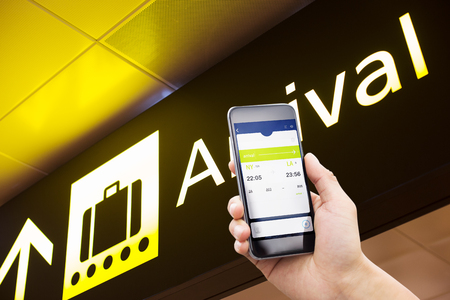 internet terminal: mobile phone with arrival sign in modern airport