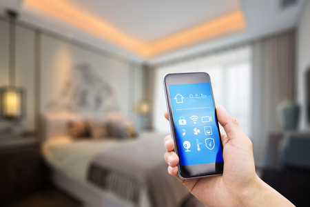 현대 침실에 똑똑한 집에 애플 리케이션과 휴대 전화 스톡 콘텐츠