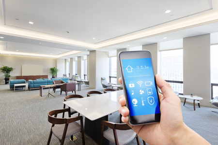 mobile phone with smart home apps in modern meeting room Banco de Imagens
