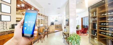mobile phone with smart home app in modern wine cellar