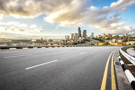 empty asphalt road and cityscape of los angeles in blue sky