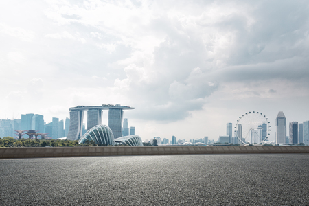 empty asphalt road and cityscape of singapore in cloud sky