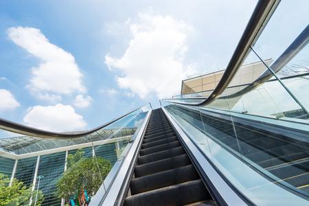 outdoors escalator near modern buildings against blue cloud sky Editorial