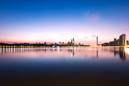 riverbank: tranquil water and beautiful reflection of modern buildings in guangzhou new city against colorful sky at twilight Stock Photo