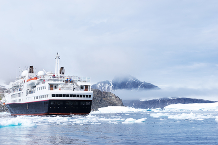 luxury passenger ship sails on icy sea in antarctic in clouds ky Stock Photo