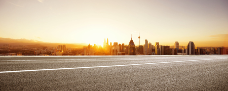 empty asphalt road and cityscape of kuala lumpur at sunrise