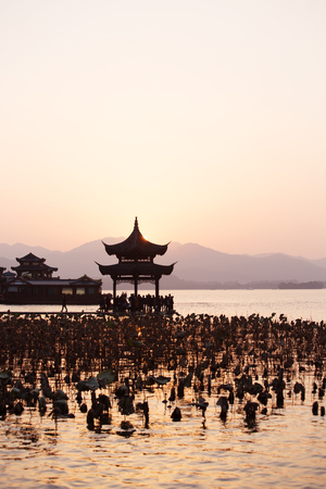 landscape of west lake with old style architecture in hangzhou at twilight.Chinese text on it only introduces itself and it is named Juxian pavilion Stock Photo