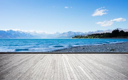empty brick floor and beautiful lake near snow mountain in blue sky Stock Photo