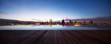 modern cityscape of kuala lumpur at twilight from swimming pool on balcony