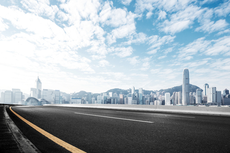 empty asphalt road and cityscape of hong kong in blue cloud sky