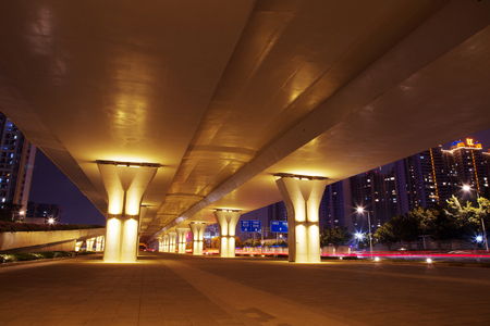 night scene of empty sidewalk below modern viaduct in guangzhou Фото со стока