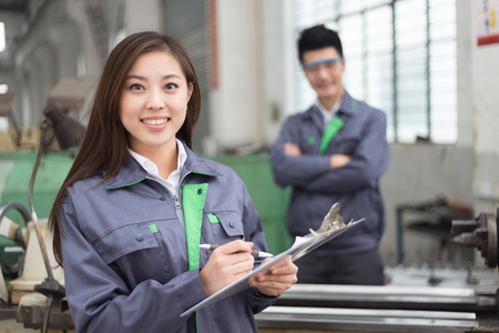 young chinese man and woman work in motor manufacturing factory