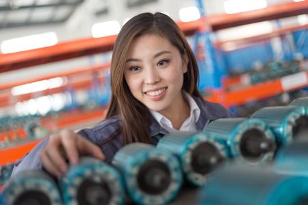 young chinese woman works in motor manufacturing factory