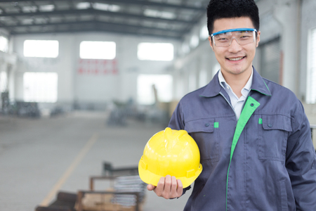 young chinese man works in motor manufacturing factory