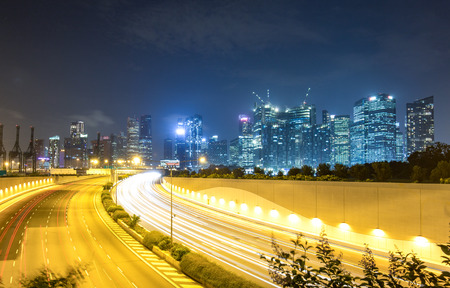 busy highway and modern buildings in midtown of singapore at night