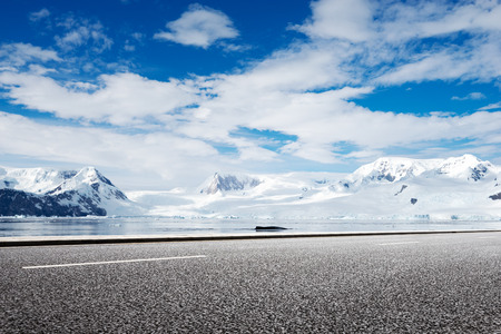 empty asphalt road with snow mountain Stock Photo