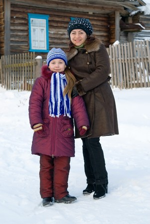 Woman with a young girl in a cap and scarf photo