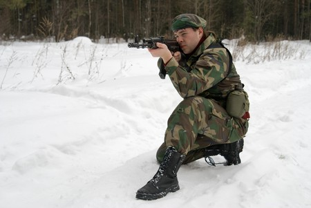 automat: A young man in a camouflage shoots from the automat of kalashnikova