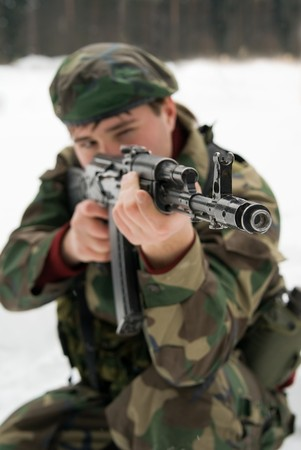 A young man in a camouflage shoots from the automat of kalashnikova Stock Photo - 4471872