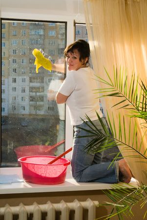 A woman washes a window in a house Stock Photo - 4702208