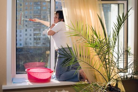 A woman washes a window in a house