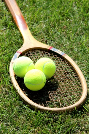 Vintage tennis racket with ball on grass court