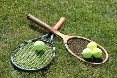 Vintage and new tennis rackets with balls on grass court  photo