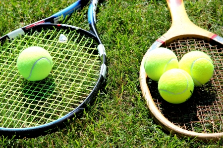 stringent: Vintage and new tennis rackets with balls on grass court