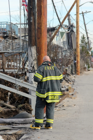 BREEZY POINT, NY - NOVEMBER 20: Firefighter assessing damage in hurricane devastated area  in the aftermath of Hurricane Sandy on November 20, 2012 in Breezy Point, NY. More than 80 houses were destroyed in out-of-control six-alarm blaze.